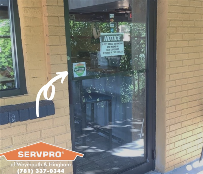 a business door with the certified servpro cleaned decal