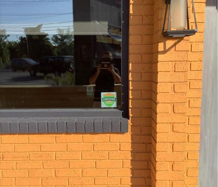a photo of a commercial building with the Certified: SERVPRO Cleaned seal in the window