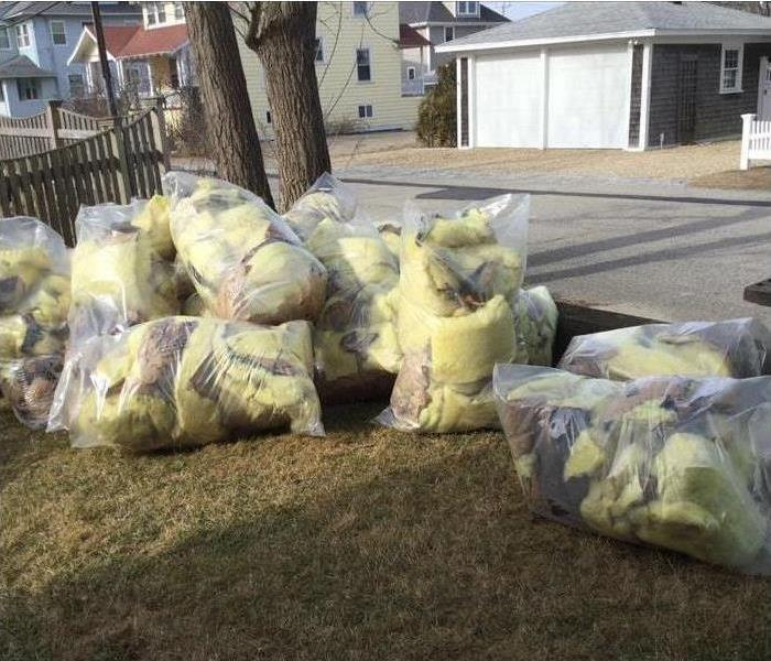 eight clear bags with damaged material from a house